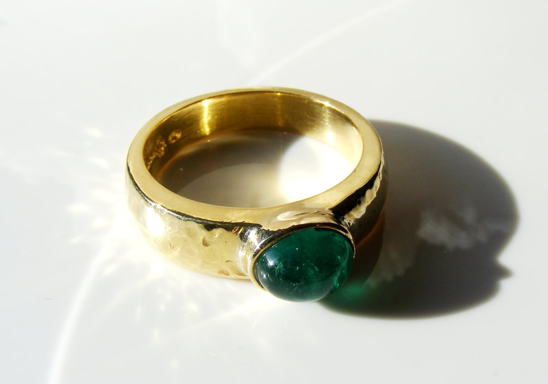 Heavy gold hammered ring with columbian emerald