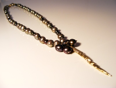 Natural dark freshwater pearls, with solid gold, flowing lava pendant.