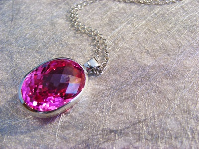 huge, bold, facetted fushia pink topaz, oval shape, set in silver with silver chain.